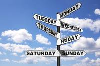 A signpost with the seven days of the week on the directional arrows, against a bright blue cloudy sky. Good image for a 24/7 related theme.